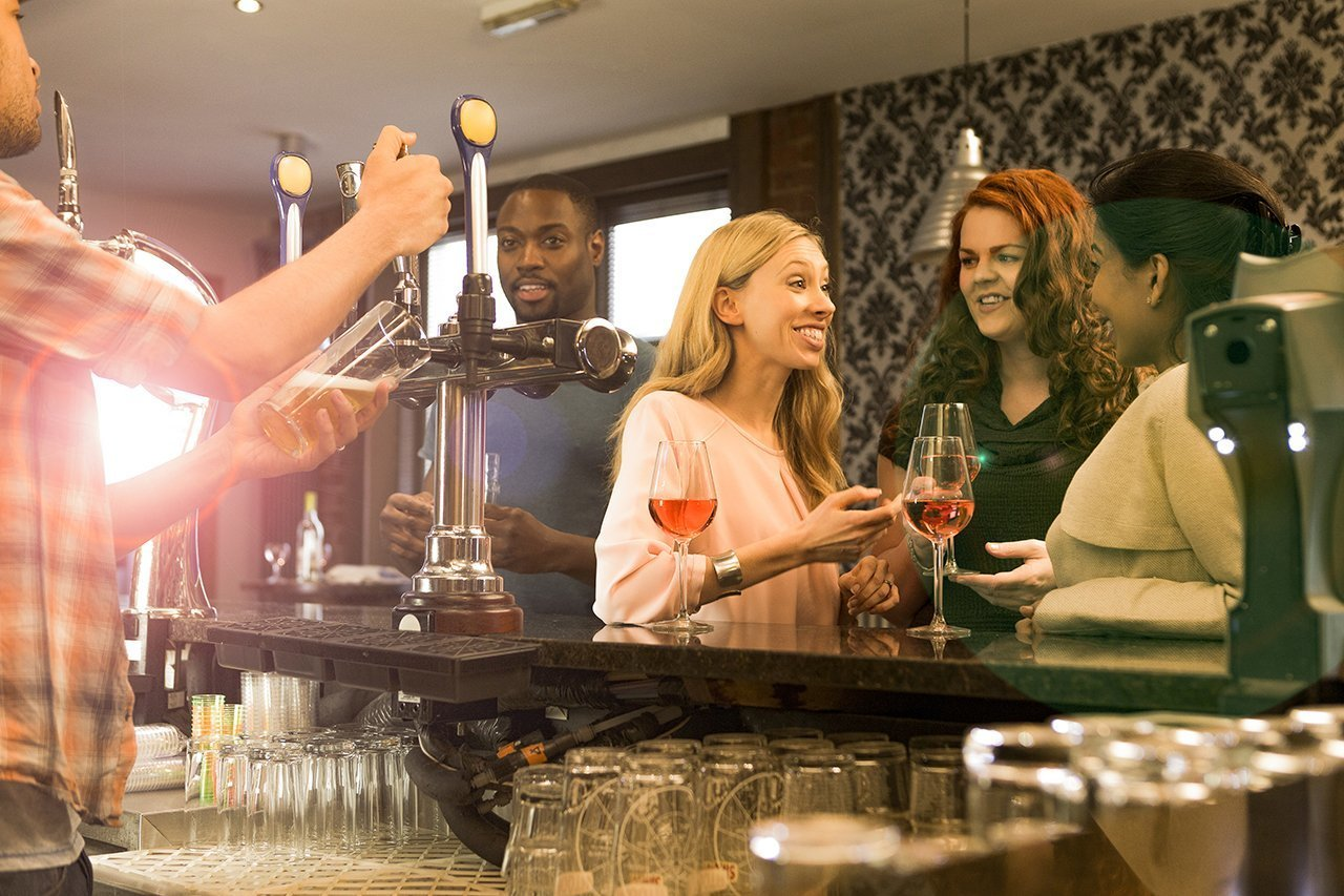 Members of the public enjoying drinks at the bar area of a busy pub