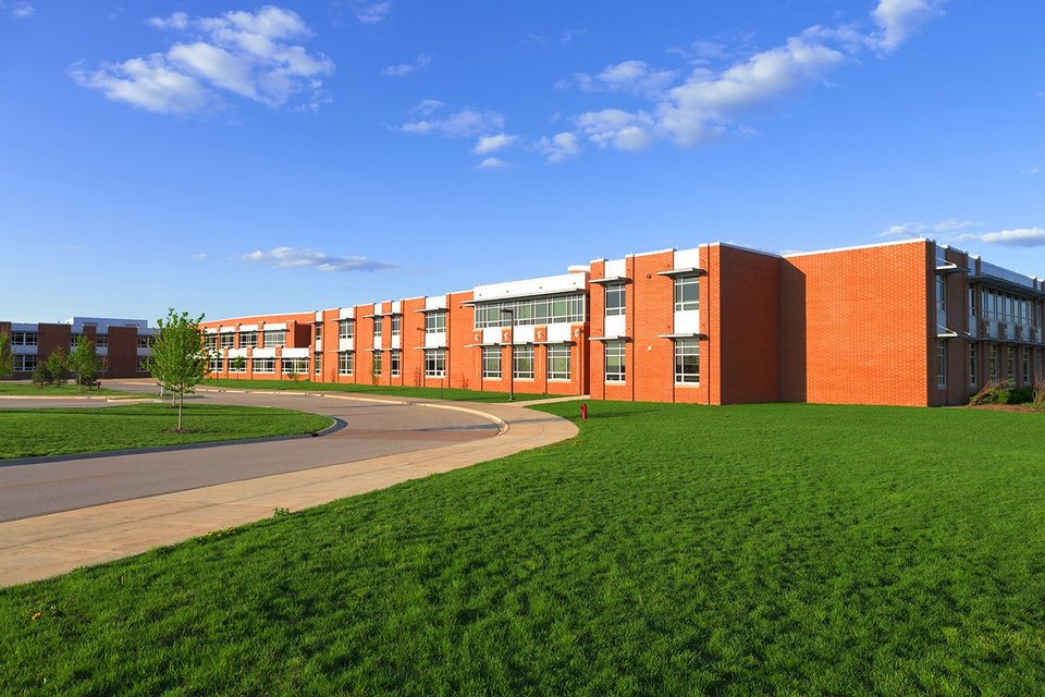 Exterior view of modern school, grass area and blue skies
